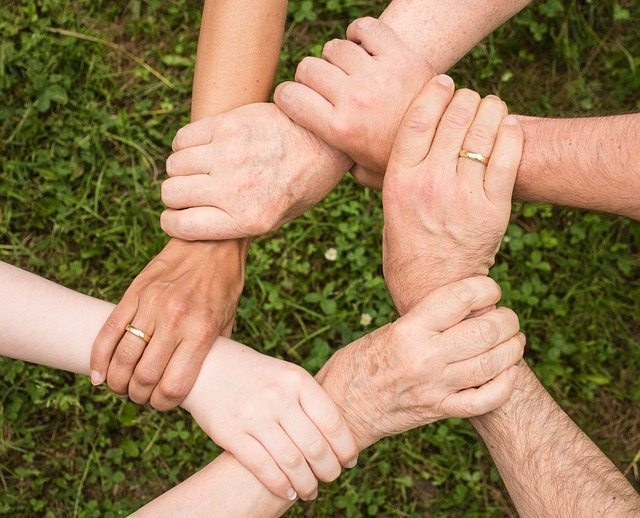 image of hands holding hands depicting it takes a village to raise a family